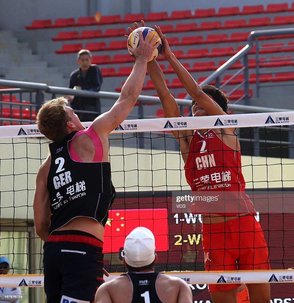 Wu Jiaxin (R) of China defends against Alexander Walkenhorst of Germany during the men's main draw of FIVB Beach Volleyball Shanghai Grand Slam at Jinshan City Beach on May 1, 2013 in Shanghai, China.