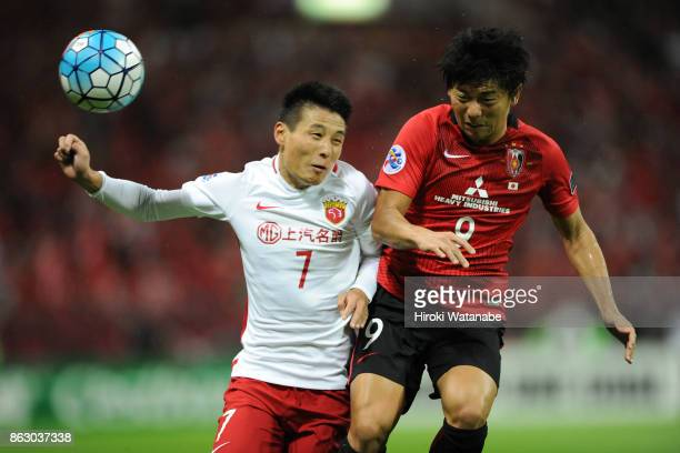 Wu Lei of Shanghai SIPG and Yuki Muto of Urawa Red Diamonds compete for the ball during the AFC Champions League semi final second leg match between...