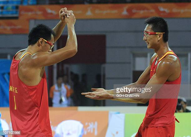 Wu Penggen and Xu Linyin of China celebrate after beating compatriots Gao Peng and Li Jian in the beach volleyball men's final match at the 16th...
