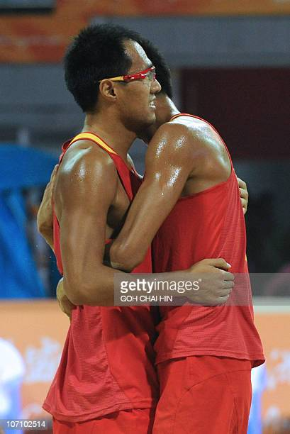Wu Penggen and Xu Linyin of China hug each other after beating compatriots Gao Peng and Li Jian in the beach volleyball men's final match at the 16th...