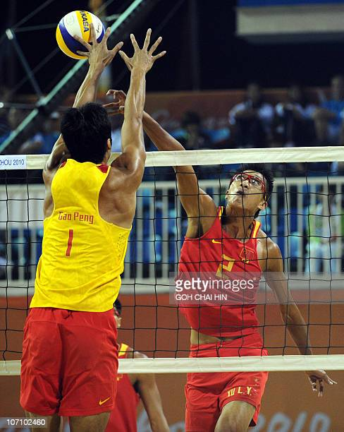 Wu Penggen of China spikes the ball pass compatriot Gao Peng during the beach volleyball men's final match at the 16th Asian Games in Guangzhou on...