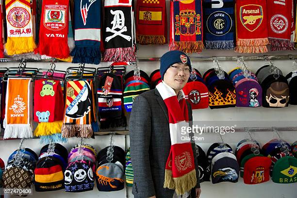 Wu Pengxu owner of the Yiwu Wells Knitting Products Co Ltd factory poses in his showroom weraing Arsenal cap and scarf in Yiwu Zhejiang Province...