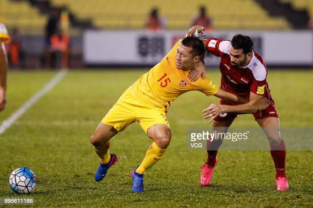 Wu Xi of China and Mhd Zaher Almedani of Syria compete for the ball during the 2018 FIFA World Cup Asian Qualifier Group A Final Round match between...