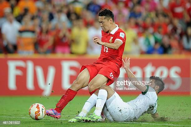 Wu Xi of China PR is tackled by Mustafa Al Bassas of Saudi Arabia during the 2015 Asian Cup match between Saudi Arabia and China PR at Suncorp...