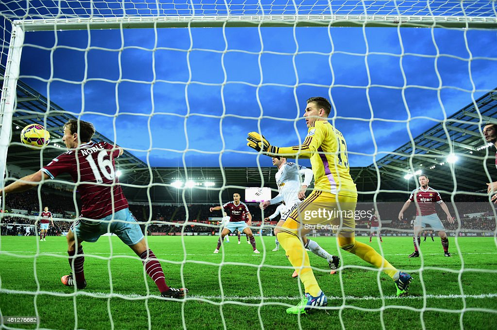 Wwest Ham player <a gi-track='captionPersonalityLinkClicked' href=/galleries/search?phrase=Mark+Noble&family=editorial&specificpeople=844055 ng-click='$event.stopPropagation()'>Mark Noble</a> (l) and goalkeeper Adrian are unable to stop a header from Bafetimbi Gomis of Swansea (hidden) going into the net for the Swansea equaliser during the Barclays Premier League match between Swansea City and West Ham United at Liberty Stadium on January 10, 2015 in Swansea, Wales.