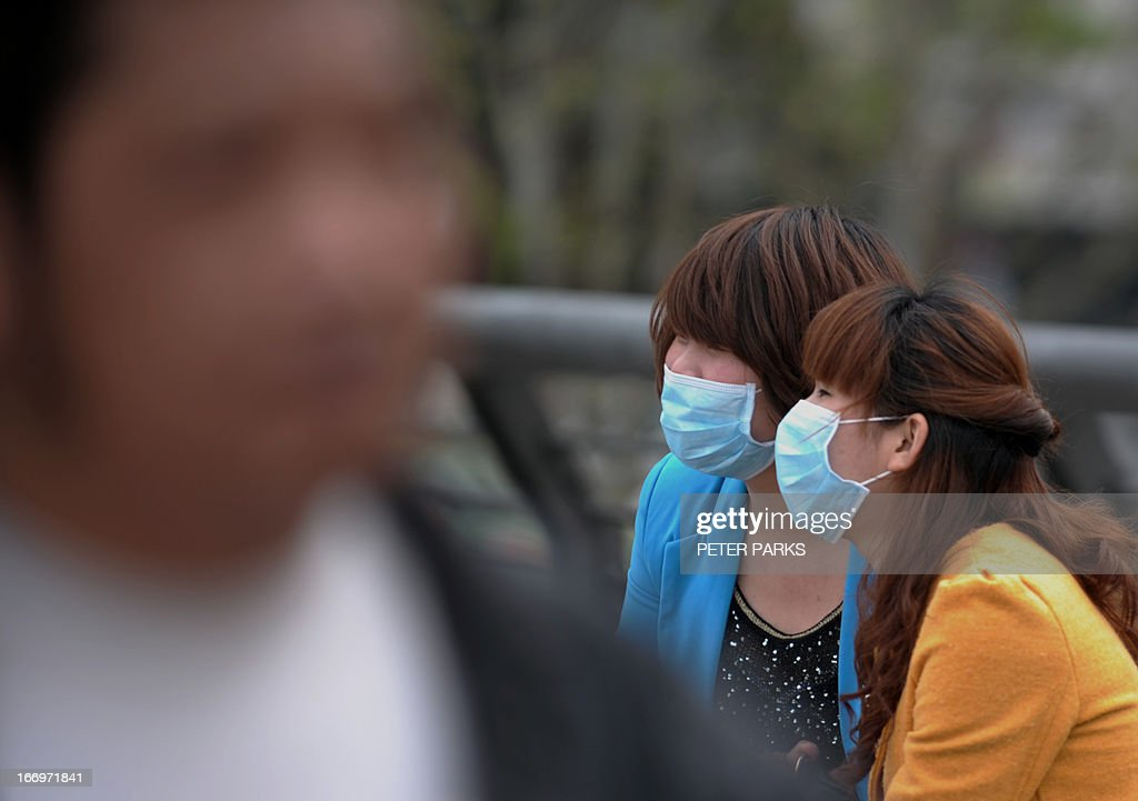 Wwomen wear face masks as they visit the historic Bund in Shanghai on April 19, 2013. Experts from the UN's health agency arrived in China on a weeklong mission in Beijing and Shanghai to examine whether the H7N9 bird flu virus is spreading among humans after a cluster of cases among relatives but downplayed fears of a pandemic on April 19. AFP PHOTO/Peter PARKS