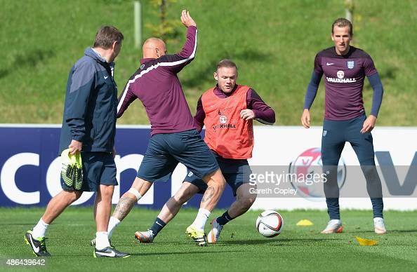 Wyane Rooney of England gets pass Jonjo Shelvey during a training session at St Georges Park on September 4 2015 in BurtonuponTrent England
