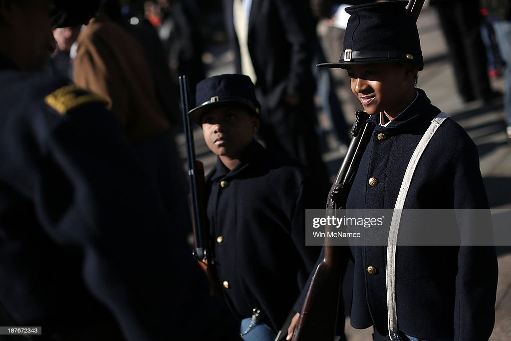 Wyatt Harris (R) and Joshua Terry (2nd R), dressed in Civil War military uniforms, participate in a wreath-laying ceremony commemorating Veterans Day and honoring the Tuskegee Airmen November 11, 2013 in Washington, DC. The ceremony was held at the African American Civil War Memorial on the day that World War I ended 95 years ago, the date the United States honors all of its military veterans.