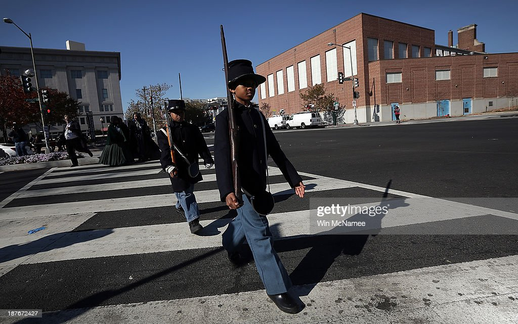 Wyatt Harris (R) and Joshua Terry (2nd R), dressed in Civil War military uniforms, cross the street after taking part in a wreath-laying ceremony commemorating Veterans Day and honoring the Tuskegee Airmen November 11, 2013 in Washington, DC. The ceremony was held at the African American Civil War Memorial on the day that World War I ended 95 years ago, the date the United States honors all of its military veterans.