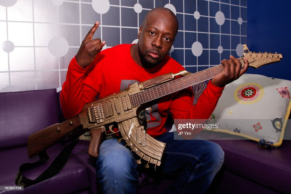 Wyclef Jen poses backstage with a guitar shaped like a AK-47 before taping a segment on BET's 106 & Park on May 1, 2013 in New York City.