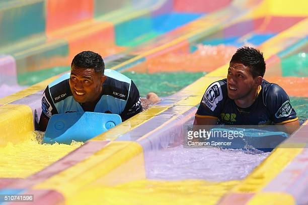 Wycliff Palu of the Waratahs and Christian Lealiifano of the Brumbies lay down on a slide during the 2016 Super Rugby Australian season launch at...