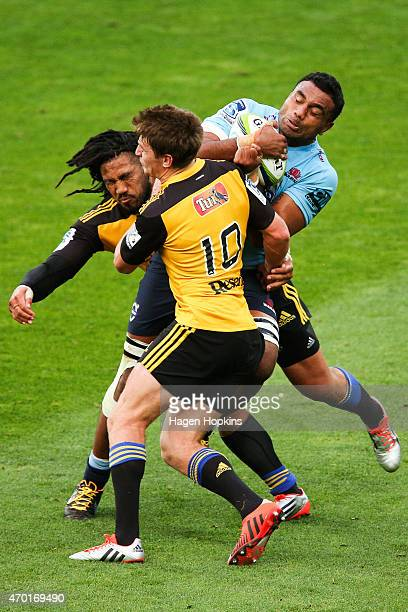 Wycliff Palu of the Waratahs is tackled by Beauden Barrett and Ma'a Nonu of the Hurricanes during the round 10 Super Rugby match between the...