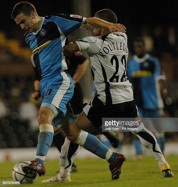 Wycombe Wanderers' Anthony Grant holds shrugs off Wayne Routledge of Fulham during the Carling Cup second round match at Craven Cottage in west London