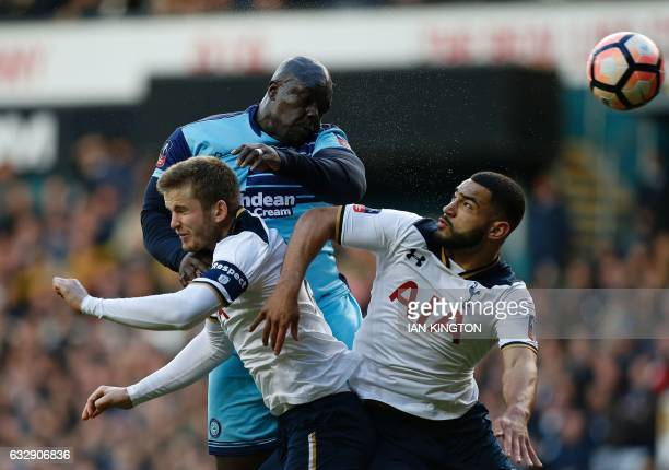 Wycombe Wanderers' English striker Adebayo Akinfenwa jumps above Tottenham Hotspur's English defender Eric Dier and Tottenham Hotspur's Englishborn...