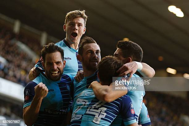 Wycombe Wanderers' English striker Paul Hayes is mobbed by teammates as he celebrates scoring from the penalty spot to score his team's second goal...
