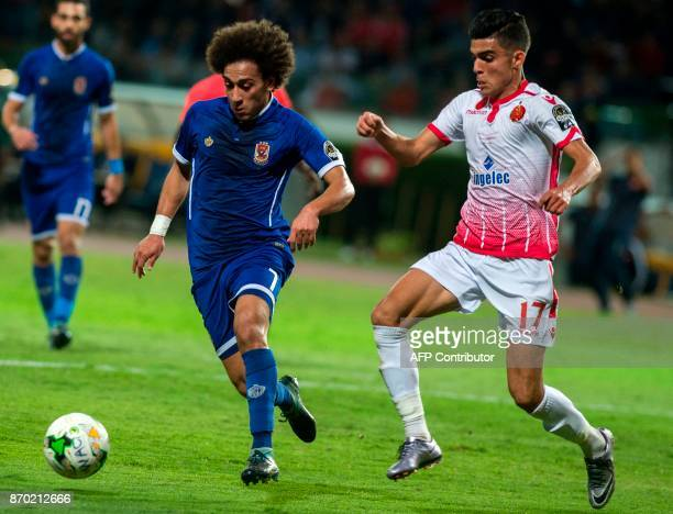 Wydad Casablanca's Achraf Bencharki vies for the ball against AlAhly's Hussein Sayed during the CAF Champions League final football match between...