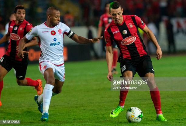 Wydad Casablanca's Brahim Nakach vies for the ball with the USM Alger's Oussama Darfalou during the CAF Campions league semifinal on October 21 at...