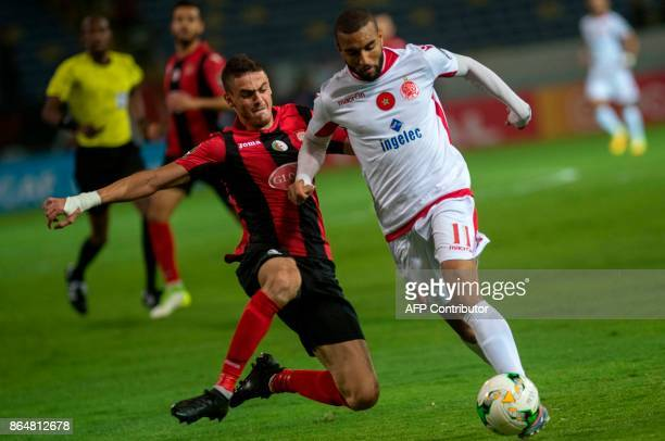 Wydad Casablanca's Ismael El Haddad vies for the ball with the USM Alger's Ayoub Abdellaoui during the CAF Campions league semifinal on October 21 at...