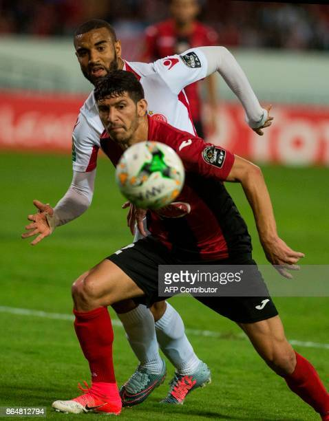 Wydad Casablanca's Ismael El haddad vises for the ball with the USM Alger's Faouzi Yaya during the CAF Campions league semifinal on October 21 at...