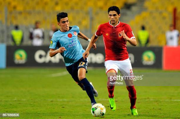 Wydad's striker Achraf Bencharki vies for the ball with Ahly's Defnder Mohamed Naguib during the CAF Champions League final football match between...