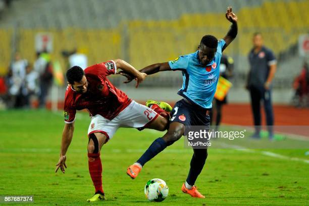 Wydad's striker Guillaume Nicaise vies for the ball with Ahly's defender Ahmed Fathi during the CAF Champions League final football match between...