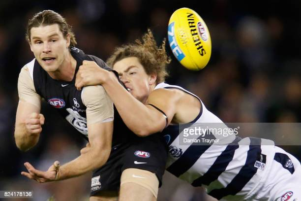 Wylie Buzza of the Cats tackles Bryce Gibbs of the Blues during the round 19 AFL match between the Carlton Blues and the Geelong Cats at Etihad...