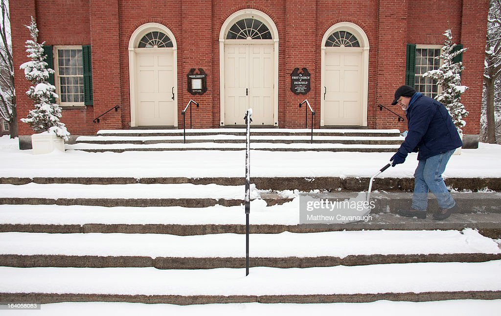 Wyn Arms shovels snow from the steps of the First Church of Deerfield on March 19, 2013 in Deerfield, Massachusetts. Another winter storm blew through the Northeast yesterday, with snow and sleet closing schools in some areas and making for a messy morning commute.