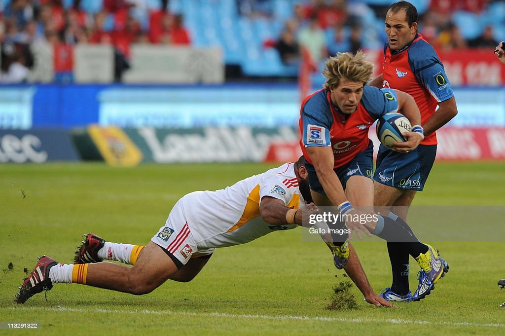 <a gi-track='captionPersonalityLinkClicked' href=/galleries/search?phrase=Wynand+Olivier&family=editorial&specificpeople=540920 ng-click='$event.stopPropagation()'>Wynand Olivier</a> of the Bulls is tackled by <a gi-track='captionPersonalityLinkClicked' href=/galleries/search?phrase=Aled+de+Malmanche&family=editorial&specificpeople=1036719 ng-click='$event.stopPropagation()'>Aled de Malmanche</a> of the Chiefs during the Vodacom Super Rugby match between Vodacom Bulls and Chiefs from Loftus Versfeld Stadium on April 30, 2011 in Pretoria, South Africa.