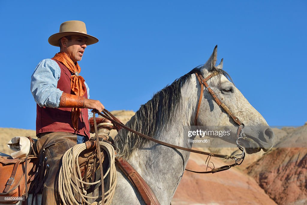 USA, Wyoming, cowboy on his horse in badlands