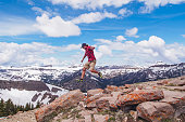 USA, Wyoming, Jackson Hole, Mid adult man jumping over rocks in mountains