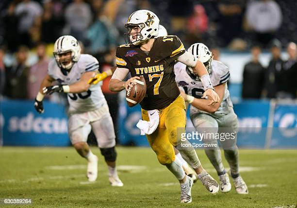 Wyoming Josh Allen scrambles away from a potential sack during the San Diego Credit Union Poinsettia Bowl game between the BYU Cougars and the...