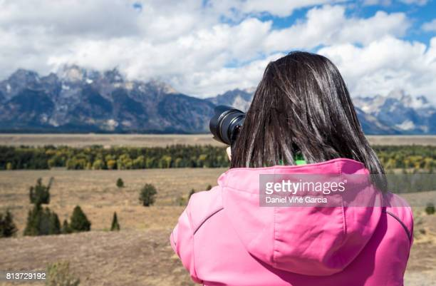 USA, Wyoming, Rocky Mountains, Grand Teton National Park, woman taking picture of Teton Range