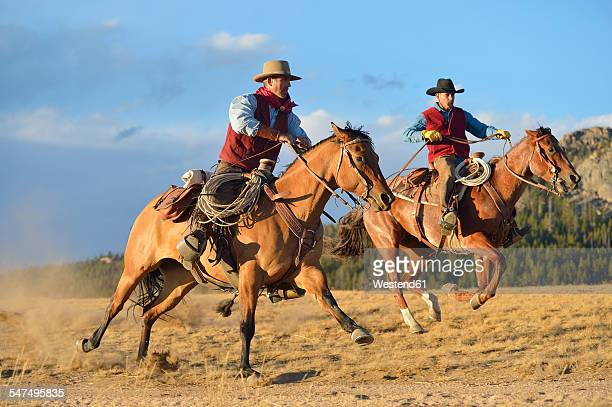 USA, Wyoming, two riding cowboys