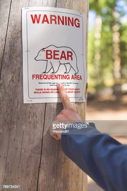 USA, Wyoming, Yellowstone National Park, hand pointing on bear warning sign