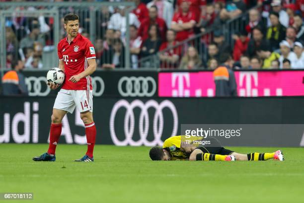 Xabi Alonso and Christian Pulisic of Dortmund looks on during the Bundesliga match between Bayern Muenchen and Borussia Dortmund at Allianz Arena on...