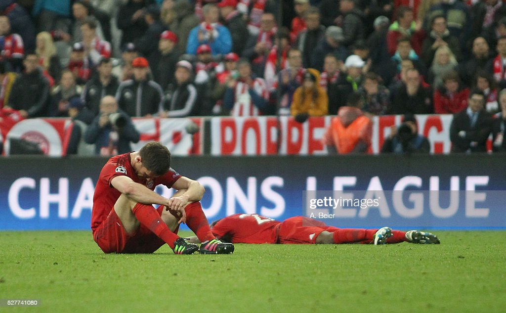 Xabi Alonso (L) and Kingsley Coman of Bayern Muenchen react after their team's loss of the Champions League semi final second leg match between FC Bayern Muenchen and Club Atletico de Madrid at Allianz Arena on May 3, 2016 in Munich, Germany.