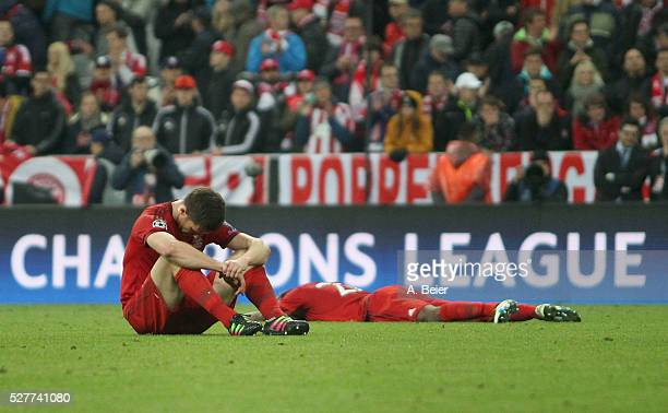 Xabi Alonso and Kingsley Coman of Bayern Muenchen react after their team's loss of the Champions League semi final second leg match between FC Bayern...
