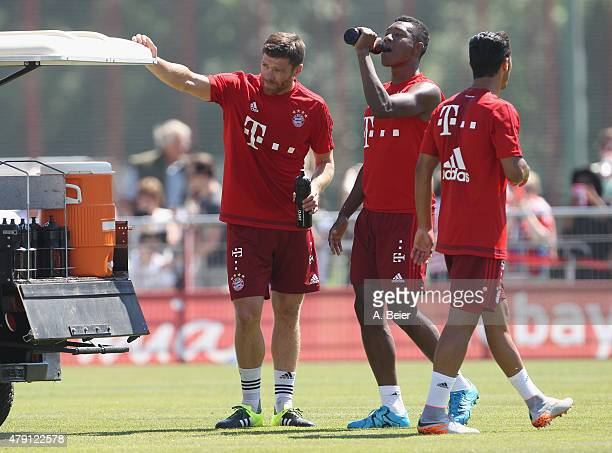 Xabi Alonso David Alaba and Thiago of Bayern Muenchen rest during the team's first training session at the FC Bayern Muenchen training ground at...