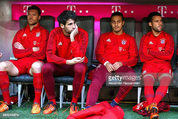 Xabi Alonso Javier Martinez Thiago and Juan Bernart of Muenchen take place on the team bench for the Bundesliga match between FC Bayern Muenchen and...