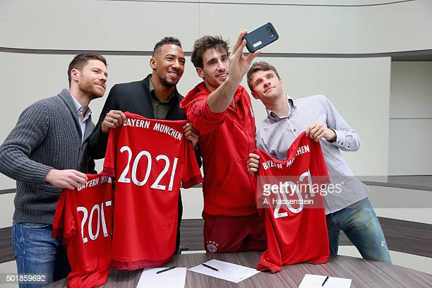 Xabi Alonso Jerome Boateng Javier Martinez and Thomas Mueller of FC Bayern Muenchen pose after signing their contract extension at FC Bayern Muenchen...