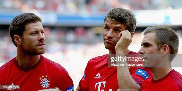 Xabi Alonso looks on with Thomas Mueller and Philipp Lahm during the FC Bayern Muenchen season opening and team presentation at Allianz Arena on July...