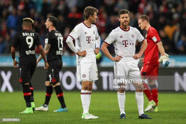 Xabi Alonso of Bayern and Thomas Mueller react after the Bundesliga match between Bayer 04 Leverkusen and Bayern Muenchen at BayArena on April 15...