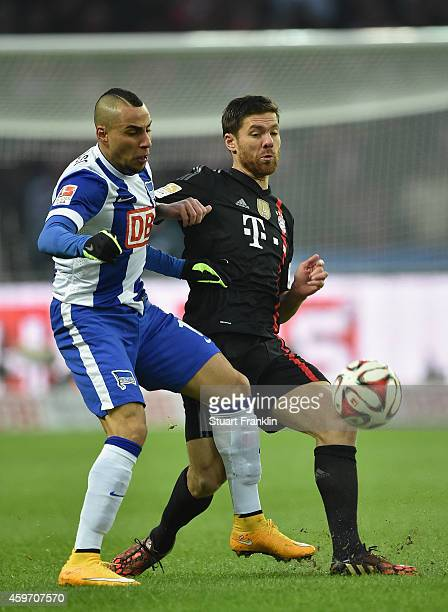 Xabi Alonso of Bayern is challenged by Anis Ben Hatira of Berlin during the Bundesliga match between Hertha BSC and FC Bayern Muenchen at...