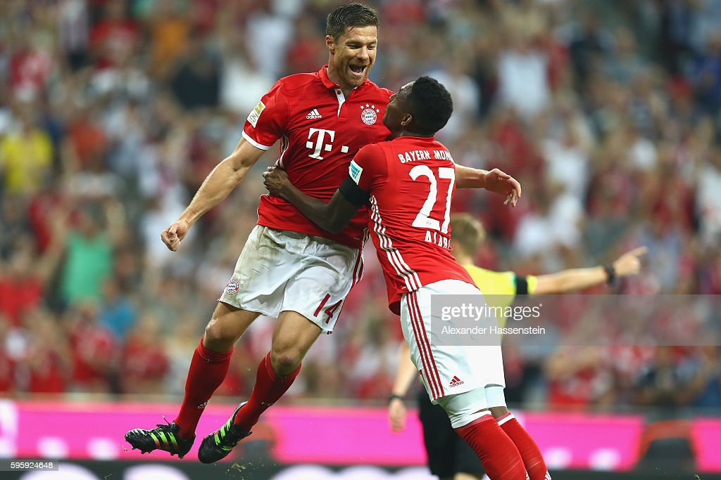Xabi Alonso (L) of Bayern Muenchen celebrates scoring the first team goal with his team mate David Alaba during the Bundesliga match between Bayern Muenchen and Werder Bremen at Allianz Arena on August 26, 2016 in Munich, Germany.
