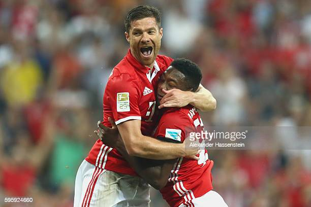 Xabi Alonso of Bayern Muenchen celebrates scoring the first team goal with his team mate David Alaba during the Bundesliga match between Bayern...