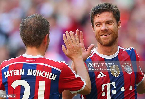 Xabi Alonso of Bayern Muenchen celebrates with Philipp Lahm of Bayern Muenchen after scoring their second goal during the Bundesliga match between FC...
