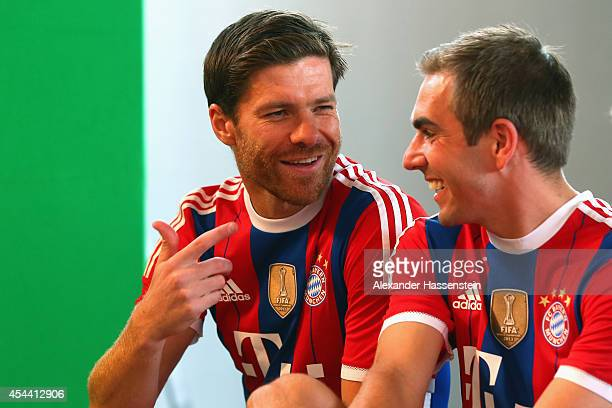 Xabi Alonso of Bayern Muenchen smiles with his team mate Philipp Lahm the FC Bayern Muenchen Paulaner photo shoot in traditional Bavarian lederhosen...