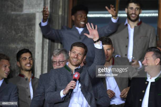 Xabi Alonso of Bayern Muenchen speaks to the fans as they celebrate winning the 67th German Championship title on the town hall balcony at...