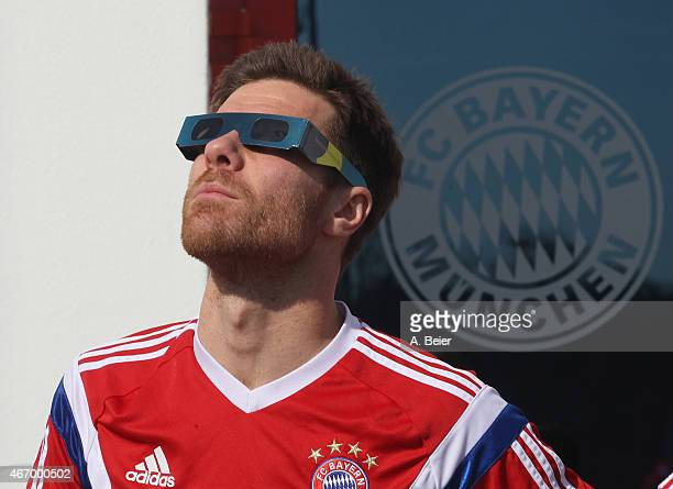 Xabi Alonso of Bayern Muenchen watches a penumbral solar eclipse before a training session at the FC Bayern Muenchen training ground on March 20 2015...