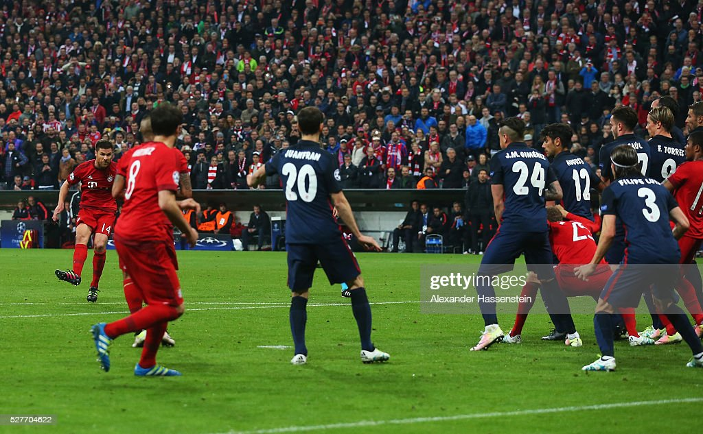 Xabi Alonso of Bayern Munich (L) scores their first goal from a free kick during UEFA Champions League semi final second leg match between FC Bayern Muenchen and Club Atletico de Madrid at Allianz Arena on May 3, 2016 in Munich, Germany.